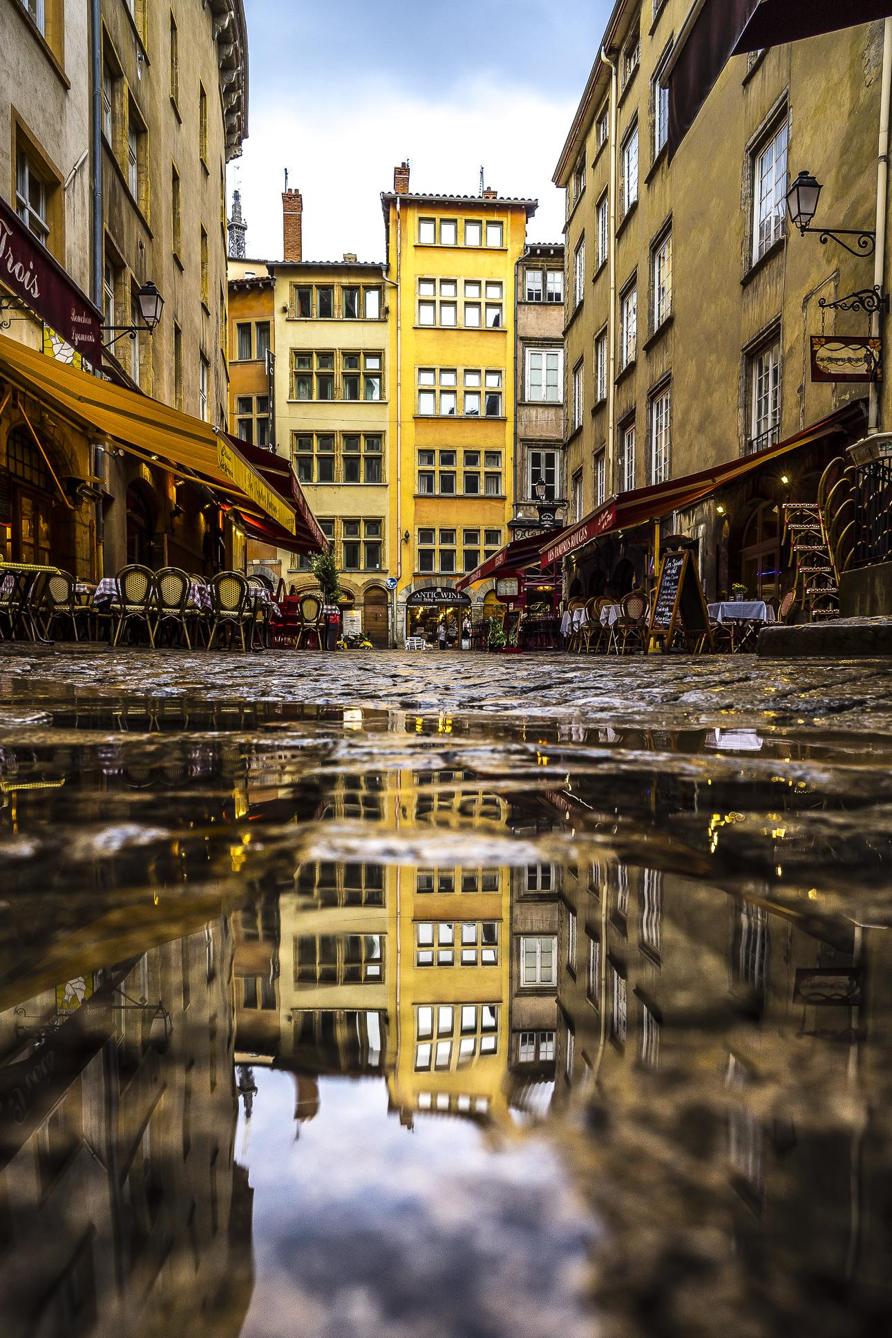 Vieux Lyon, France - Place Neuve Saint-Jean reflecting in a puddle