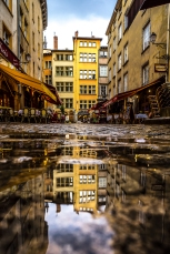 Vieux Lyon, France - Place Neuve Saint-Jean reflecting in a puddle
