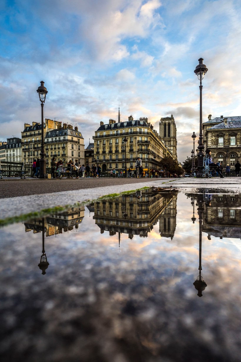 Paris, France - Notre-Dame de Paris reflecting in a puddle on Pont d'Arcole