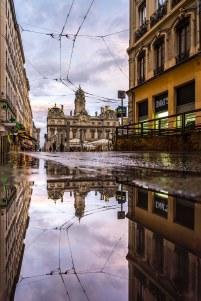 Lyon, France - Hôtel de Ville reflecting in a puddle
